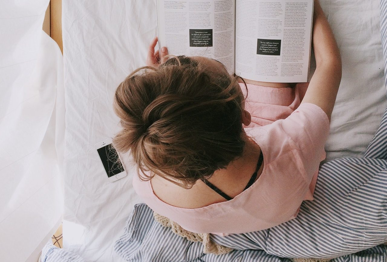 woman reading a magazine in bed
