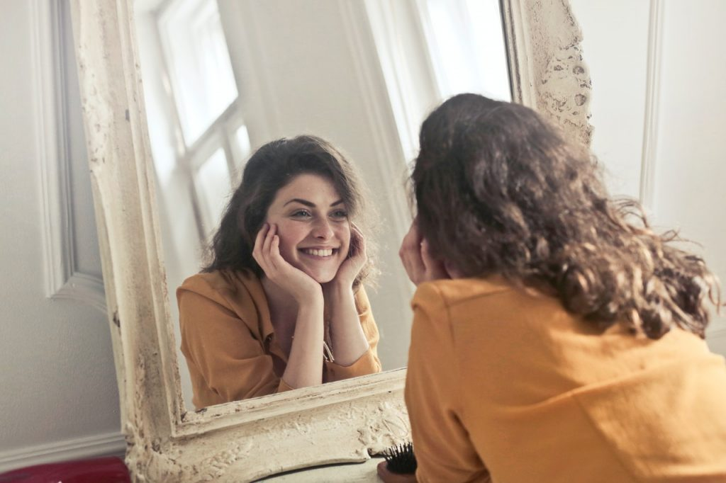 woman smiling to herself in a mirror