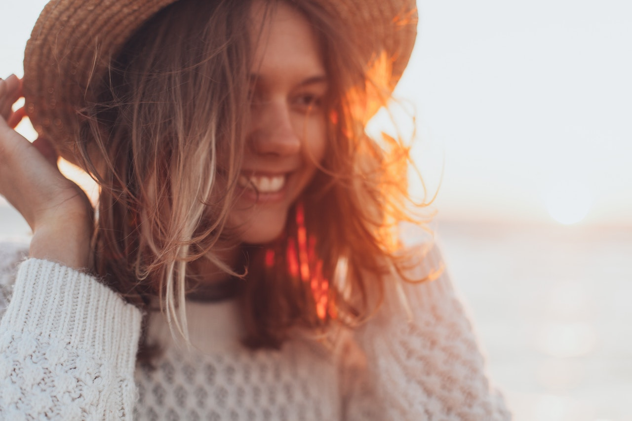 image of a woman smiling who is wearing a straw hat