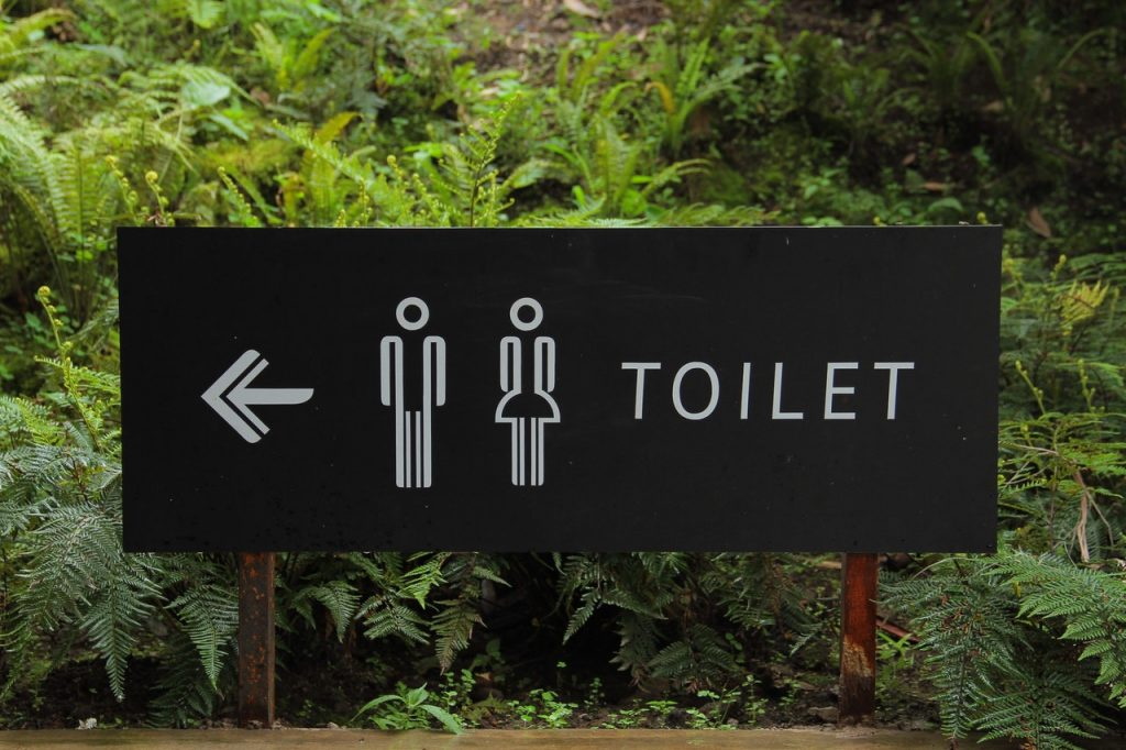 sign with directions to a toilet
