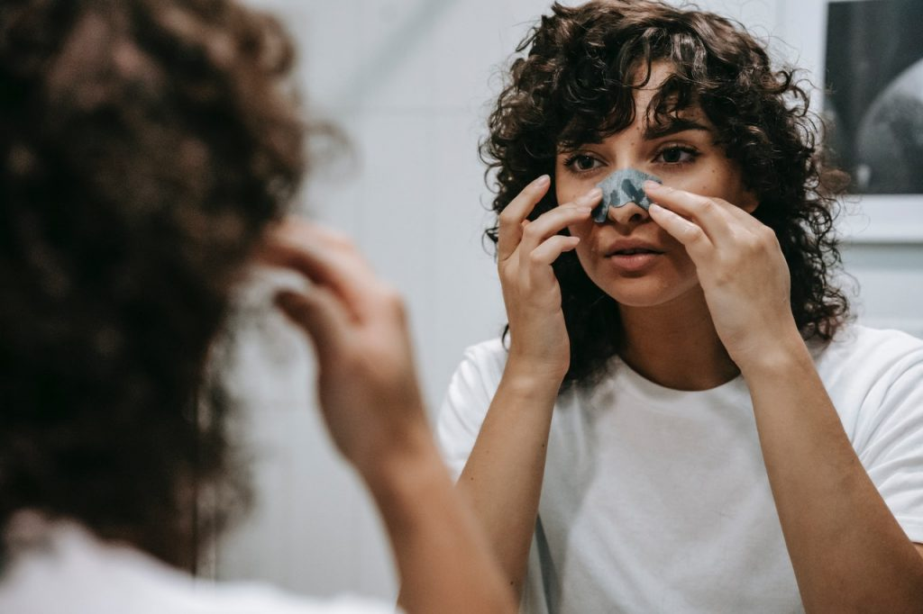 woman putting on a nose strip looking in a mirror