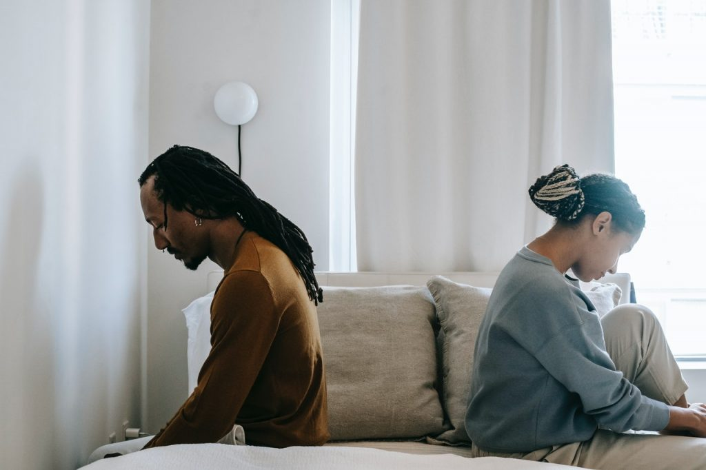 man and woman sat back to back on a bed