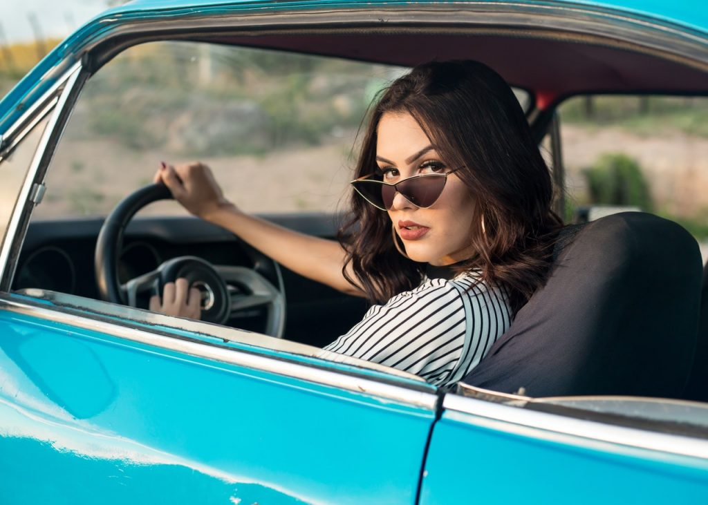 woman in a blue car looking back