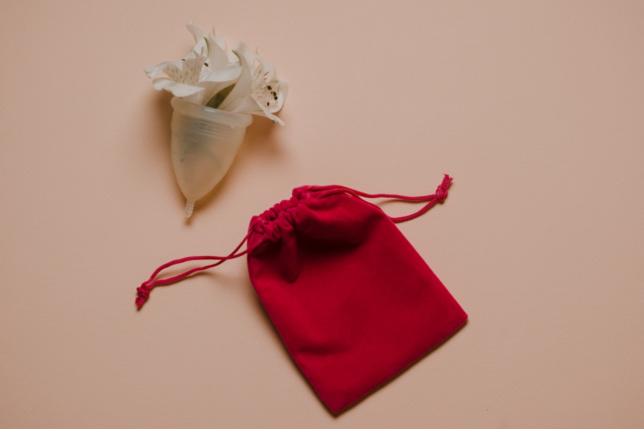menstrual cup with a red bag